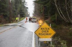 Nöd- arbetarvägbesättning som förlägger varningstecken på den översvämmade huvudvägen Faror efter en regnstorm arkivfoto