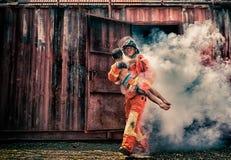 Nöd- brandräddningsaktionutbildning, brandmän sparar pojken från bu arkivfoto