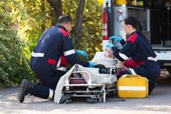 Nöd- medicinsk personal som räddar patienten Arkivbild