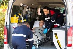 Nöd- medicinsk personal som transporterar patienten Arkivfoton