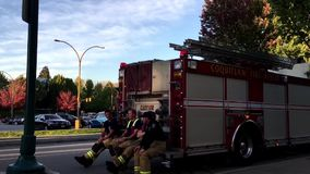 Nöd- personaler för Coquitlam brand som vilar och pratar på brandlastbilen stock video