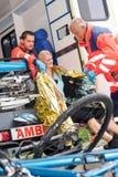 Nödlägeperson med paramedicinsk utbildning som hjälper kvinnacykelolycka Arkivbild