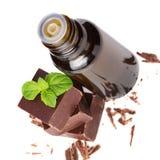 Nödvändig nödvändig olja och choklad med minten lämnar isolerat Royaltyfri Foto