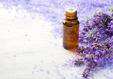 Nödvändig olja för lavendel, kvistar av lavendel och mineralbadsalt på trätabellen Selektivt fokusera arkivfoto