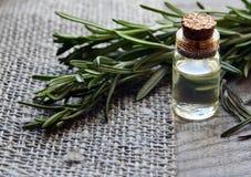 Nödvändig olja för rosmarin i en glasflaska med den nya gröna rosmarinörten på den gamla trätabellen Rosmarinolja för brunnsorten Fotografering för Bildbyråer