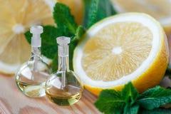 Nödvändig olja i glasflaska med ny saftig citronfrukt och gröna sidor av mintkaramellen på träbakgrund olja för badskönhetsammans Royaltyfri Bild