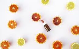 Nödvändig olja med apelsiner, lägenhet lägger på vit bakgrund Royaltyfri Foto