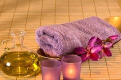 Nödvändig olja, stearinljus, handduk och purpura blommor. Arkivbild