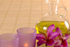 Nödvändig olja, stearinljus och purpura blommor. Arkivbild