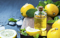 Nödvändig olje- flaska för citron med citronfrukter och mintkaramellsidor royaltyfri foto