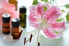 Nödvändiga oljor med den rosa liljan Arkivfoton