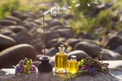Nödvändiga oljor och aromatiska pinnar för meditation på en vagga arkivbilder