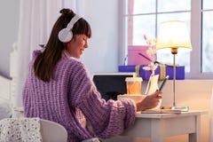 Nöjd brunettflicka som gör hennes hem- uppgift royaltyfri bild