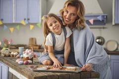 Nöjd dam och barn som visar deras kulinariska talang royaltyfri foto