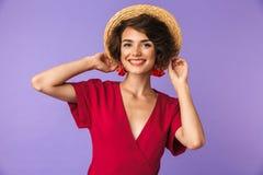 Nöjd elegant kvinna, i att posera för klänning- och sugrörhatt royaltyfri bild