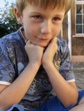 Nöjd fundersam ung pojke utomhus royaltyfri bild