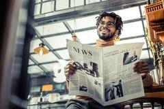 Nöjd internationell manlig person som gör pressgranskning arkivbild