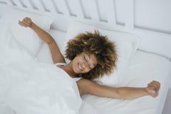 Nöjd kvinnauppvaknande i säng Arkivfoto