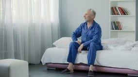 Nöjd man i hans 50-tal som sitter på soffan och ler efter morgongymnastik Arkivfoton