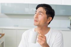 Nöjd man som dricker kaffe, som han ser bort i kök Arkivfoton