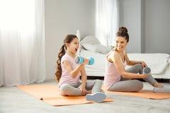 Nöjd moder och flicka som gör övningar med handvikter Arkivbilder