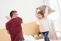 Nöjd pappa och flicka som har en kuddestrid Royaltyfri Fotografi