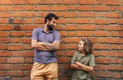Nöjd son och fader som utanför lutar mot en tegelstenvägg royaltyfria foton