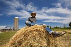 Nöjd ung bonde på den runda balen Arkivfoton