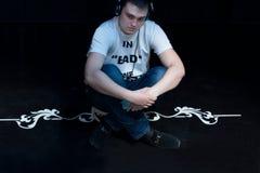 Nöjd ung man som lyssnar till musik Arkivbild