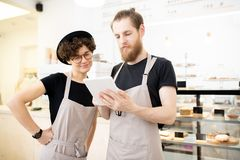 Nöjd ung personal av coffee shop som kontrollerar beställning på minnestavlan royaltyfri fotografi