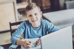 Nöjd unge som gör hem- uppgift med nöje royaltyfri foto