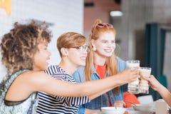 Nöjda gruppkompisar som trycker på exponeringsglas med kakao arkivfoto