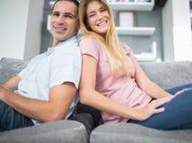 Nöjda par som tillbaka sitter för att dra tillbaka på soffan tillsammans Arkivfoto