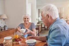 Nöjda pensionärer som tillsammans äter en sund frukost hemma Arkivbild