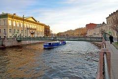 Nöjefartyget svävar under den Pochtamtsky bron över Moikaen r Royaltyfri Bild