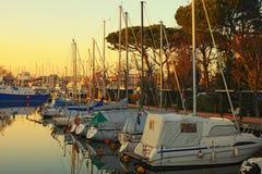 Nöjeyachter och seglar fartyg i porten av Cesenatico på solnedgång Royaltyfri Fotografi