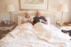 Nöjt högt parsammanträde i säng som dricker tillsammans kaffe arkivfoton