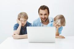 Nöjt roligt fadersammanträde med söner nära bärbara datorn som håller ögonen på på skärmen med tillfredsställt lyckligt leende me royaltyfri fotografi