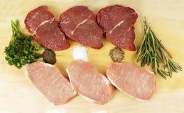 Nötkött och griskött på brädet Arkivfoto