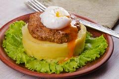 Nötkött- och grisköttliten pastej med det tjuvjagade ägget, den slog potatisen och grönsallat Arkivbild