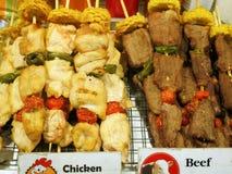 Nötkött och höna på steknålar för att grilla på räknaren shoppar arkivbilder