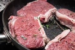 Nötkött och rosmary på stekpannan Arkivbild