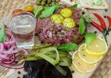 Nötkött som är tartare med vaktelägg, kapris och olika mellanmål och ett skott av vodka royaltyfri fotografi