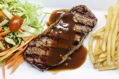 Nötköttbiff med den skivapotatisen och grönsaken Arkivbild