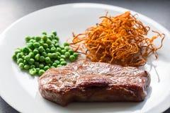 Nötköttbiff med gröna ärtor och sötpotatisen Royaltyfri Foto