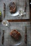 Nötköttbiff som grillas på en glass platta Exponeringsglas av vin, grönsaker Arkivbild