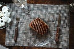 Nötköttbiff som grillas på en glass platta Exponeringsglas av vin, grönsaker Arkivfoto