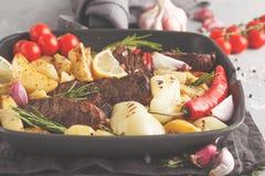 Nötköttbiffar grillade med bakade potatisar och grönsaker i en panna Royaltyfri Foto