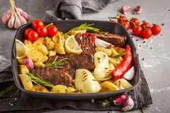 Nötköttbiffar grillade med bakade potatisar och grönsaker i en panna Fotografering för Bildbyråer