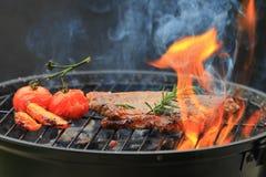 Nötköttbiffar med rosmarin på galler med flamman och rök på mörker royaltyfria foton